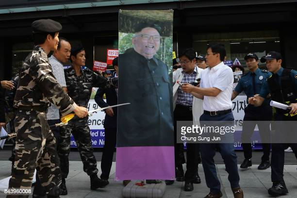 Defectors from North Korea now living in South Korea try to tear a portrait of North Korean leader Kim JongUn during a rally on September 8 2017 in...