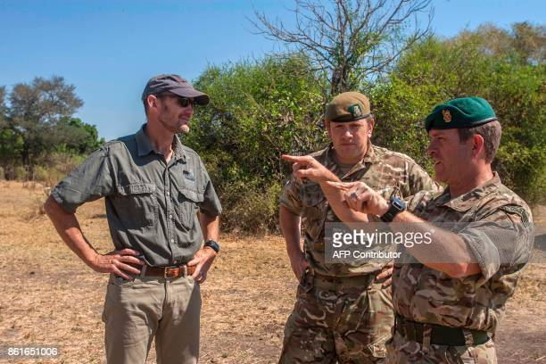 Defence Attache for British High Commission in Malawi Royal Marines Commando Colonel Mike Geldard gestures as he speaks with British Major Counter...