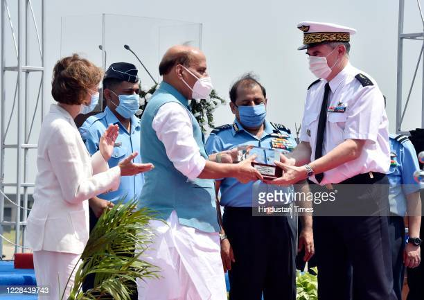Defence Minister Rajnath Singh presents a momento during the induction ceremony of Rafale Aircrafts, at Indian Army Force Airbase on September 10,...