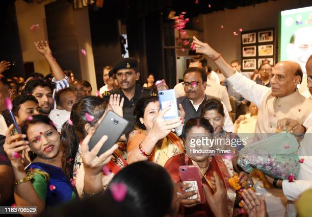 Defence Minister Rajnath Singh showers petals on BJP workers with the party's women workers takng selfies at BJP Karyakarta Abhinandan Samaroh at CMS...
