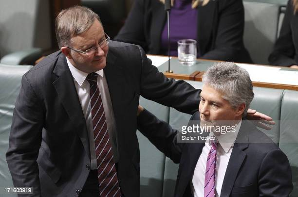 Defence Minister Stephen Smith receives a pat on the back from Deputy Prime Minister Anthony Albanese after announcing he will not contest his seat...