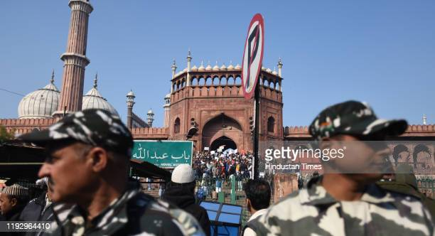 Defence personnel stand guard as people hold placards during a protest against Citizenship Amendment Act National Population Register National...