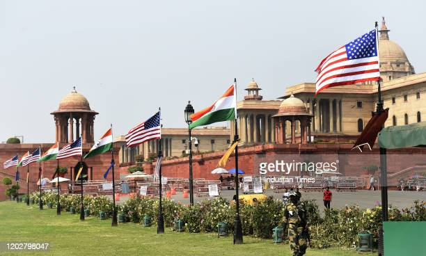 Defence personnel walks past Indian and US national flags placed on light posts ahead of US President Donald Trumps visit, near Rashtrapati Bhavan,...