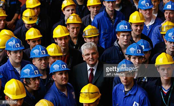 Defence Secretary Des Browne stands with workers at the Govan shipyard as they received a new Ministry of Defence contract worth an estimated 32...