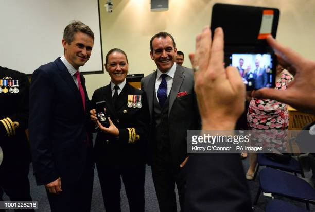 Defence Secretary Gavin Williamson poses for a photograph with Lieutenant Commander Lindsey Waudby and her partner after presenting new Operation...