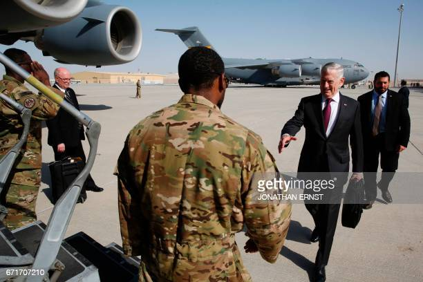 Defence Secretary James Mattis prepares to shake hands with an airman prior to boarding a US Air Force C-17 plane en route to visit a US military...