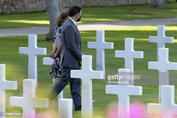 Defence Secretary Mark Esper and his wife Leah, mask-clad due to the COVID-19 coronavirus pandemic, walk past graves as they visit the North Africa...