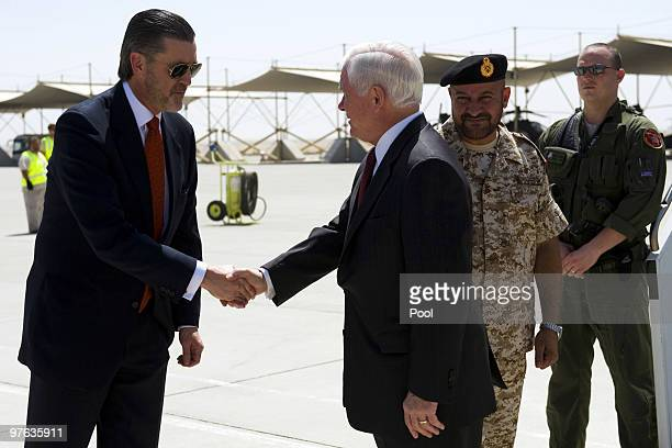 Defence Secretary Robert Gates shakes hands with US Ambassador to the UAE Richard Olson after being greeted by Emirati Deputy Chief of Staff Major...