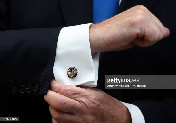 Defence Secretary Sir Michael Fallon shows off his cufflinks after cutting steel on the first Type 26 frigate at BAE System's Govan Shipyard near...