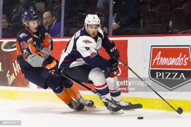 Defenceman Connor Corcoran of the Windsor Spitfires moves the puck against forward Connor Roberts of the Flint Firebirds on December 3 2017 at the...