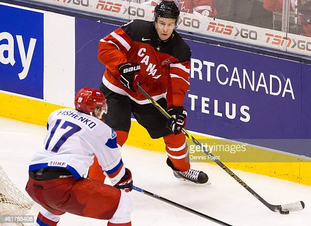 Defenceman Dillon Heatherington of Canada moves the puck against Ivan Fishenko of Russia during the Gold medal game of the 2015 IIHF World Junior...