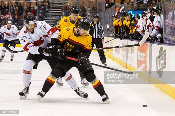 Defenceman Edson Harlacher of Switzerland battles for the puck against forward Fabio Pfohl of Germany during the 2015 IIHF World Junior Championship...