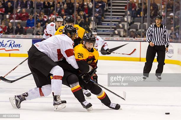 Defenceman Edson Harlacher of Switzerland skates against forward Fabio Pfohl of Germany during the 2015 IIHF World Junior Championship on January 03...