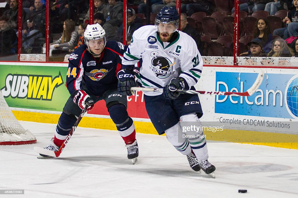 Defenceman Gianluca Curcuruto #32 of the Plymouth Whalers moves the puck against forward Luke Kirwan #44 of the Windsor Spitfires on February 18, 2015 at the WFCU Centre in Windsor, Ontario, Canada.