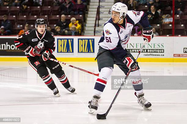 Defenceman Jalen Chatfield of the Windsor Spitfires moves the puck against forward Mikkel Aagaard of the Niagara Ice Dogs on November 22 2015 at the...