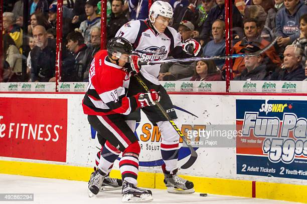 Defenceman Logan Stanley of the Windsor Spitfires battles for the puck against forward Travis Konecny of the Ottawa 67's on October 15 2015 at the...