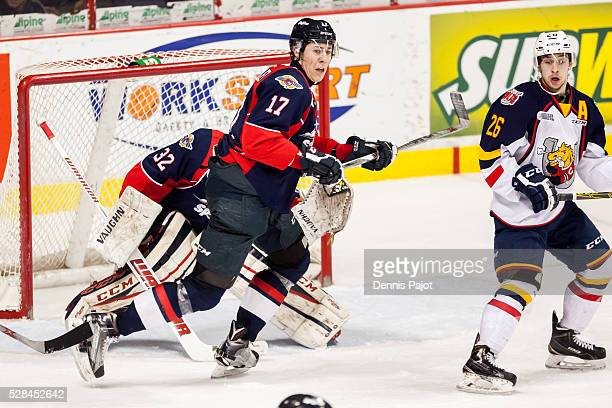 Defenceman Logan Stanley of the Windsor Spitfires battles in front of the net against forward Andrew Mangiapane of the Barrie Colts on February 25...