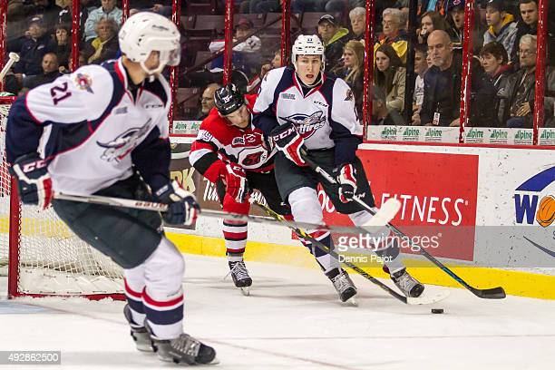 Defenceman Logan Stanley of the Windsor Spitfires moves the puck against forward Travis Barron of the Ottawa 67's on October 15 2015 at the WFCU...