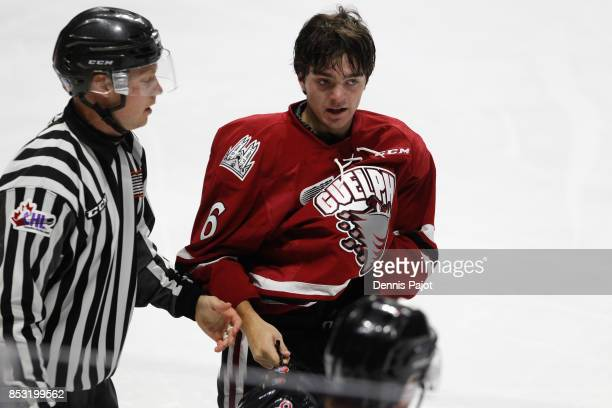 Defenceman Ryan Merkley of the Guelph Storm is escorted to the penalty box during a game against the Windsor Spitfires on September 24 2017 at the...