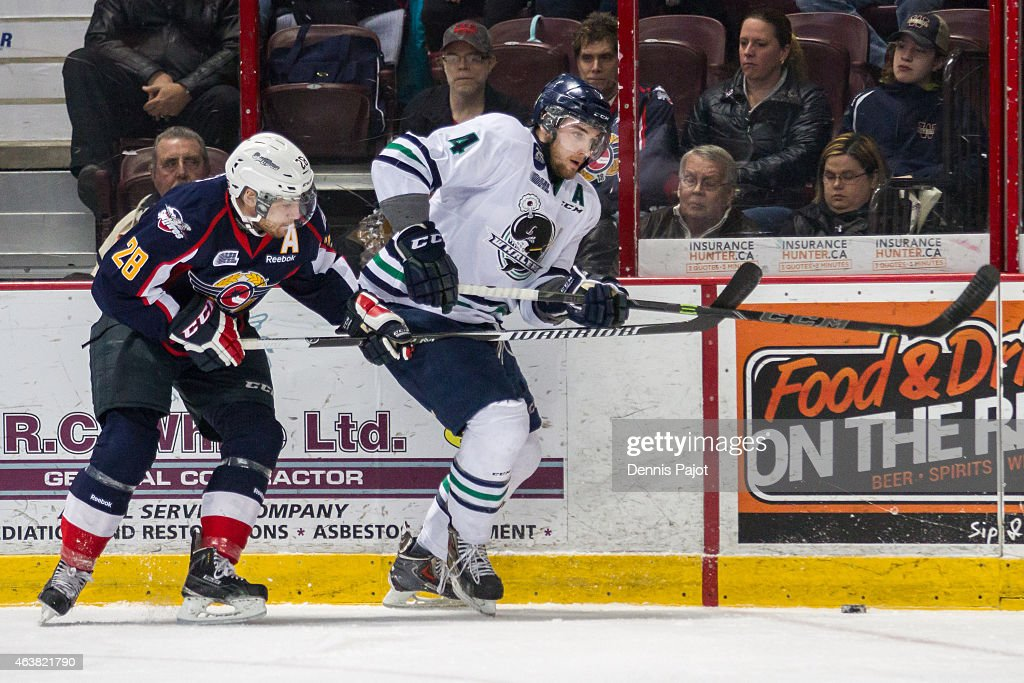 Defenceman Sean Callaghan #4 of the Plymouth Whalers battles for the puck against forward Slater Doggett #28 on February 18, 2015 at the WFCU Centre in Windsor, Ontario, Canada.