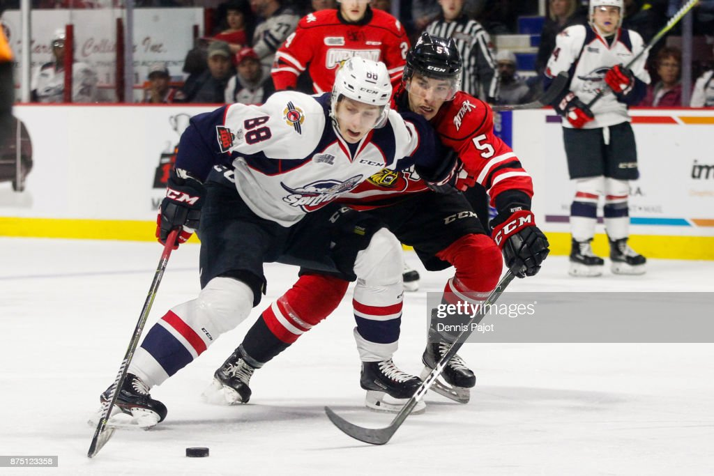 Defenceman Sean Durzi #5 of the Owen Sound Attack battles for the puck against forward Kirill Kozhevnikov #88 of the Windsor Spitfires on November 16, 2017 at the WFCU Centre in Windsor, Ontario, Canada.