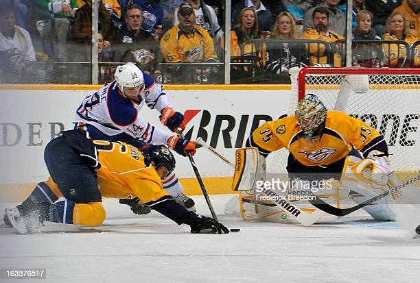 Defenceman Shea Weber of the Nashville Predators ties up Jordan Eberle of the Edmonton Oilers in front of goalie Pekka Rinne at Bridgestone Arena on...