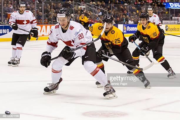 Defenceman Simon Kindschi of Switzerland skates against forward Fabio Pfohl of Germany during the 2015 IIHF World Junior Championship on January 03...