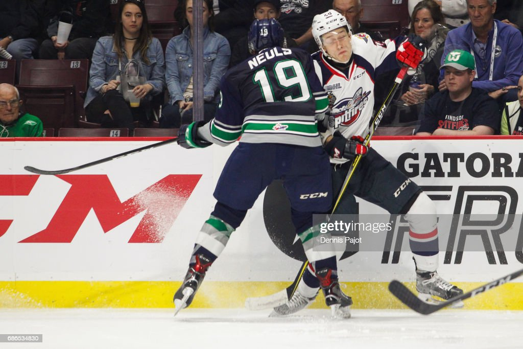 Defenceman Tyler Nother #28 of the Windsor Spitfires is checked against the boards by forward Donovan Neuls #19 of the Seattle Thunderbirds on May 21, 2017 during Game 3 of the Mastercard Memorial Cup at the WFCU Centre in Windsor, Ontario, Canada.