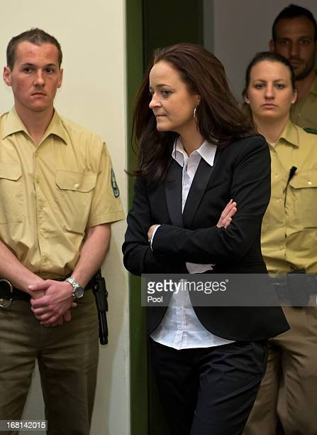 Defendant Beate Zschaepe enters court with law enforcement officers on the first day of the NSU neoNazi murder trial on May 6 2013 in Munich Germany...