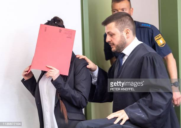 Defendant Jennifer W hides her face behind a folder and walks next to her lawyer Ali Aydin as she arrives at court for the opening of her trial on...