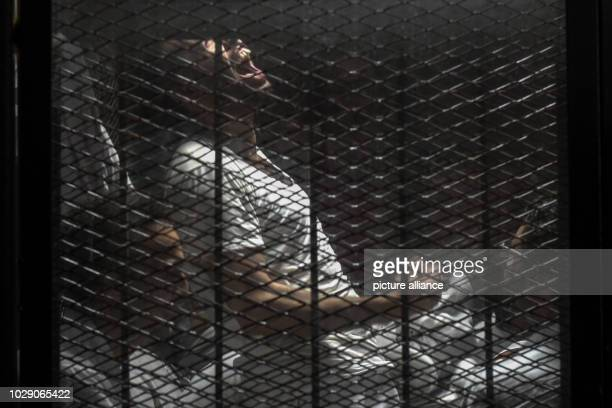 Defendant reacts as Egyptian photojournalist Mahmoud Abu Zeid , also known as 'Shawkan', sits in the defendants cage after a verdict sentenced him to...