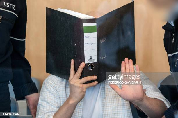Defendant Sief Allah H holds a folder in front of his face at the start of his trial on June 7 2019 at a court in Duesseldorf western Germany The...