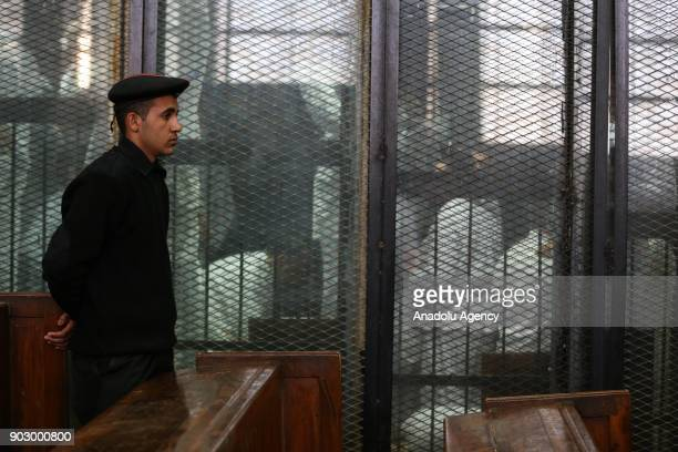 Defendants attend the trial session behind a cage in Cairo Egypt on January 9 2018 An Egyptian court slapped some 268 people with jail terms in...