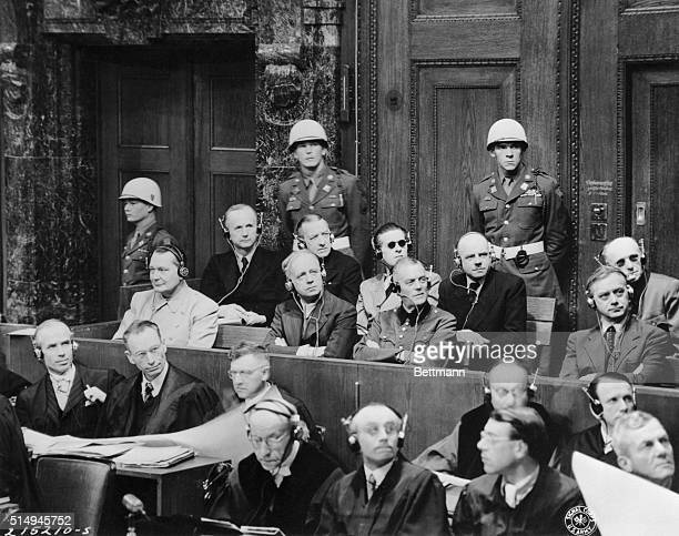 Defendants sit up and take notice at the Nuremberg war crimes trials as they stare intently at a chart of the Nazi party organization which was...