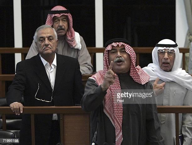 Defendants Sultan Hashim Ahmad alTai center right Sabir alDouri left Ali Hassan alMajid second left and Farhan Mutlaq Saleh right argue with the...