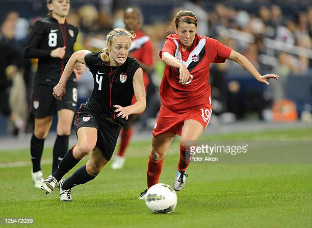 Defender Becky Sauerbrunn of the United States chases down a loose ball against pressure from mid-fielder Chelsea Stewart of Canada during the second...