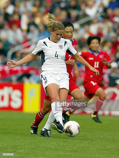 Defender Cat Reddick of the USA is pressured by forward Kum Suk Ri of North Korea during the 2003 FIFA Women's World Cup at Crew Stadium on September...