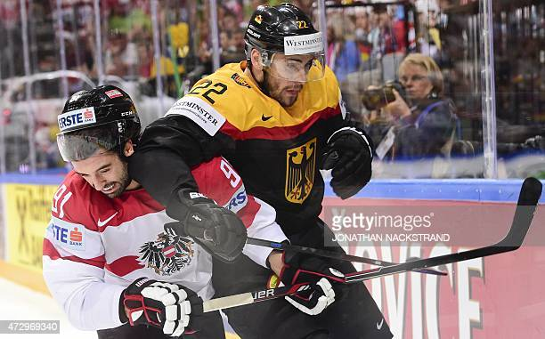 Defender Dominique Heinrich of Austria and forward Matthias Plachta of Germany vie during the group A preliminary round match Germany vs Austria at...