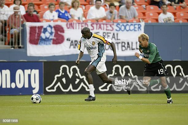 Defender Ezra Hendrickson of the Los Angeles Galaxy dribbles the ball while being pursued by midfielder Chris Henderson of the Colorado Rapids during...