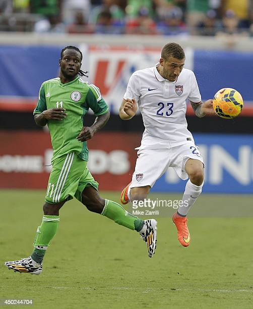 Defender Fabian Johnson of the United States heads the ball while foward Victor Moses of Nigeria looks on during the international friendly match at...