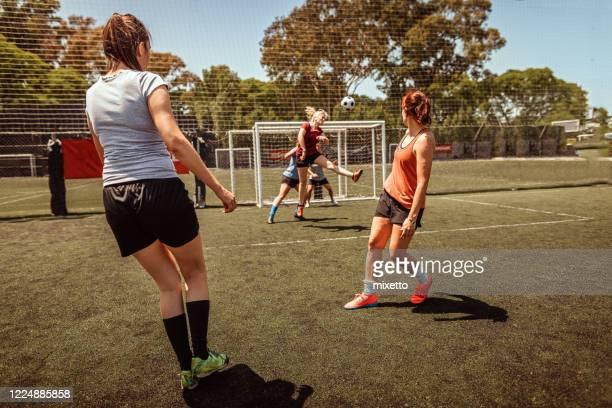 defensor a la jugadora de fútbol femenino dirige el balón durante el partido - fútbol femenino fotografías e imágenes de stock