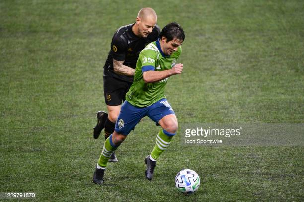 Defender Jordan Harvey defends against Seattle Sounders midfielder Nicolas Lodeiro during a MLS Cup Playoff between the Seattle Sounders and LAFC on...