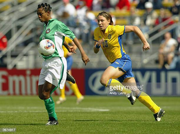 Defender Kikelomo Ajayi of Nigeria brings the ball upfield under pressure from forward Hanna Ljungberg of Sweden during the 2003 FIFA Women's World...