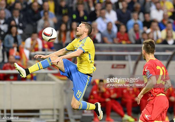 Defender Marko Simic of Montenegro observes as forward Marcus Berg of Sweden controls the ball during the Euro qualifying football match between...
