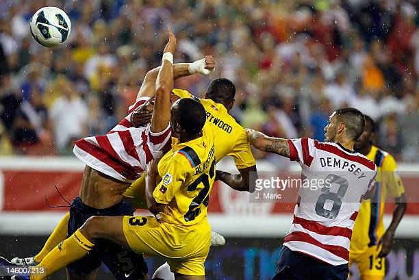 Defender Oguchi Onyewu and forward Clint Dempsey of Team USA battle for the ball in front of the goal of Team Antigua and Barbuda during the FIFA...