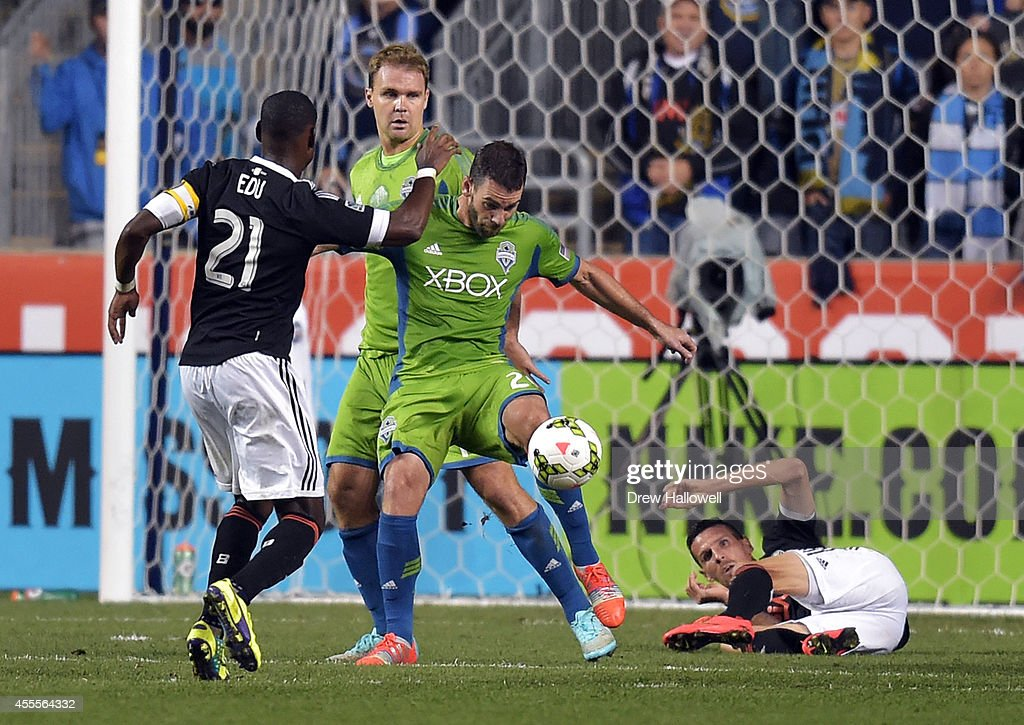 Defender Zach Scott #20 of the Seattle Sounders FC clears the ball away from midfielder Maurice Edu #21 and a fallen forward Sebastien Le Toux #11 of the Philadelphia Union during the 2014 U.S. Open Cup Final at PPL Park on September 16, 2014 in Chester, Pennsylvania. The Sounders won 3-1.