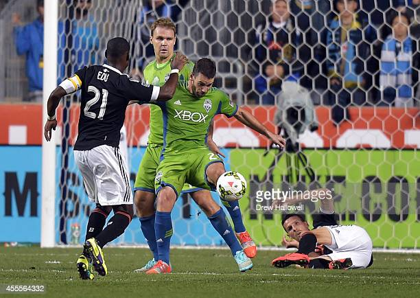 Defender Zach Scott of the Seattle Sounders FC clears the ball away from midfielder Maurice Edu and a fallen forward Sebastien Le Toux of the...