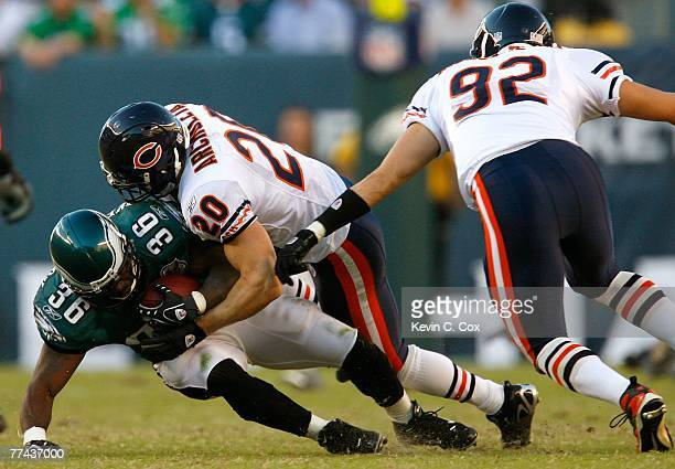 Defenders Adam Archuleta and Hunter Hillenmeyer of the Chicago Bears tackle running back Brian Westbrook of the Philadelphia Eagles during the first...