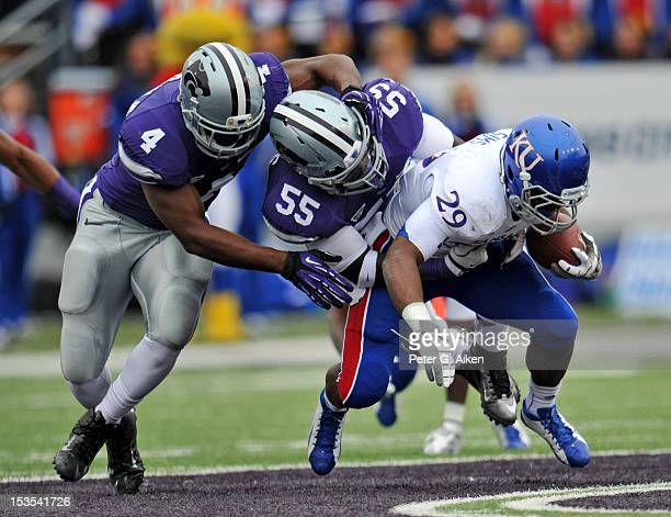 Defenders Adam Davis and Arthur Brown of the Kansas State Wildcats tackle running back James Sims of the Kansas Jayhawks for a loss during the first...