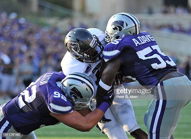 Defenders Adam Davis and Vai Lutui of the Kansas State Wildcats tackle running back Ryan Heaston of the Missouri State Bears during the first quarter...